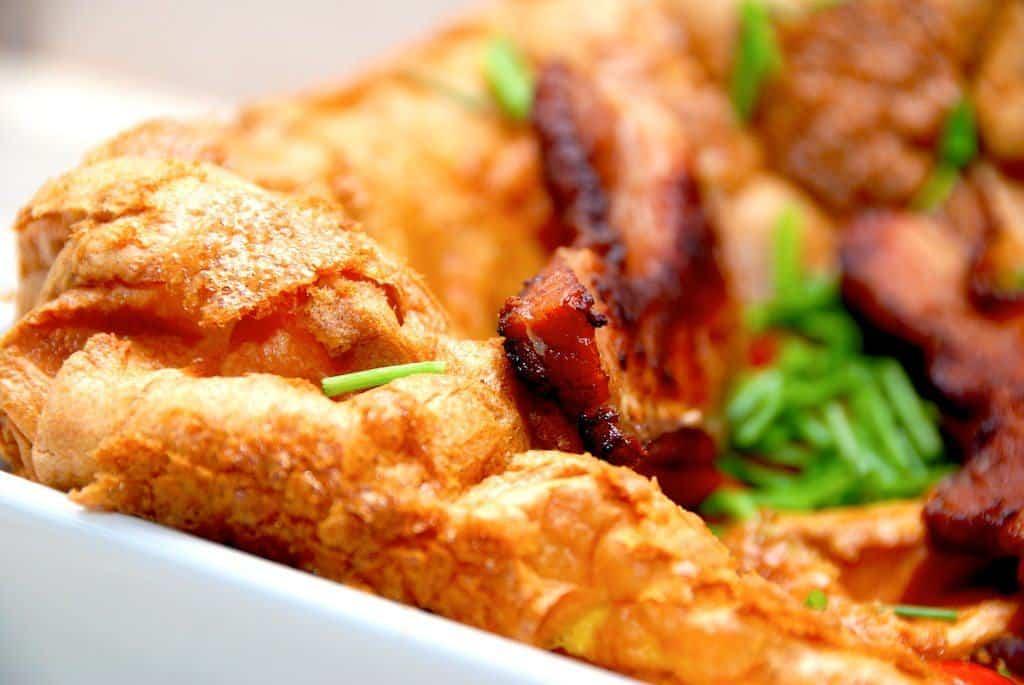 Den rigtige æggekage i ovn. Let og luftig, og godt afbagt, så den får masser af smag. Serveres pyntet med sprød bacon, friskklippet purløg og tomater i skiver. Det er verdens bedste æggekage. Foto: Guffeliguf.dk.