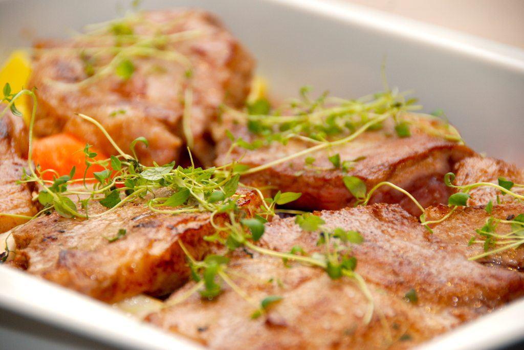 Langtidsstegte nakkekoteletter i ovn giver meget mørt kød. Her er nakkekoteletterne stegt i ovnen på en bund af forskellige rodfrugter. Foto: Guffeliguf.dk.