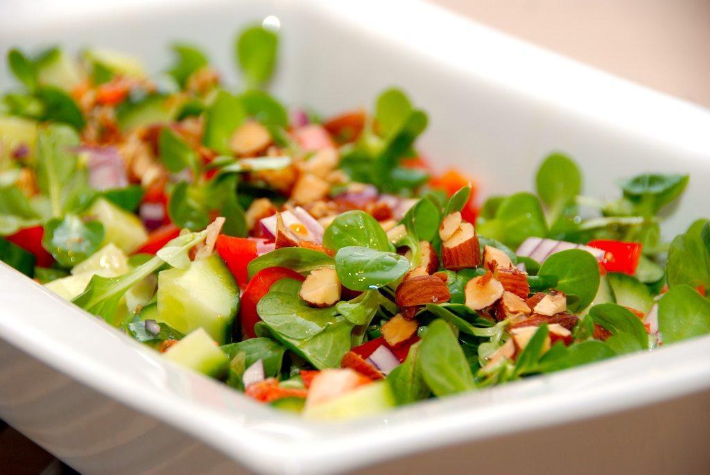 Salat med feldsalat og tomat. En dejlig salat, der også indeholder rødløg, peberfrugt og mandler. Hæld også lidt olivenolie og citronsaft over. Foto: Guffeliguf.dk.