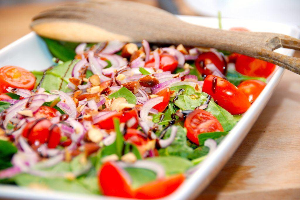 Virkelig skøn salat med spinat, tomater, rødløg og mandler. Spinatsalaten dryppes med lidt olie og balsamico. Foto: Guffeliguf.dk.