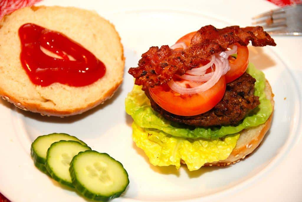 Verdens bedste burger med hjemmelavet burgerbolle, en god burgerbøf, og selvfølgelig salat, tomat, agurk og sprød bacon. Bedre bliver det ikke. Foto: Madensverden.dk.