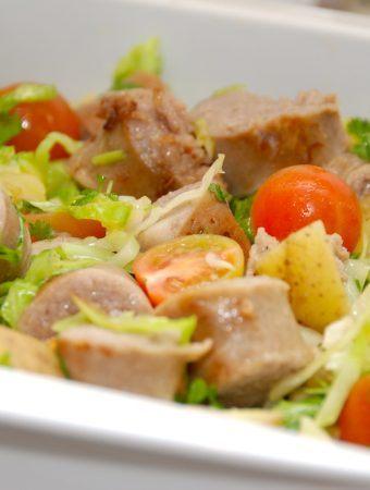 Medister i fad er nem hverdagsmad, der steges i ovnen. Medisterpølsen koges og brunes af, inden den vendes med kartofler, spidskål og tomater i et ildfast fad, og steges i ovnen. Foto: Madensverden.dk.