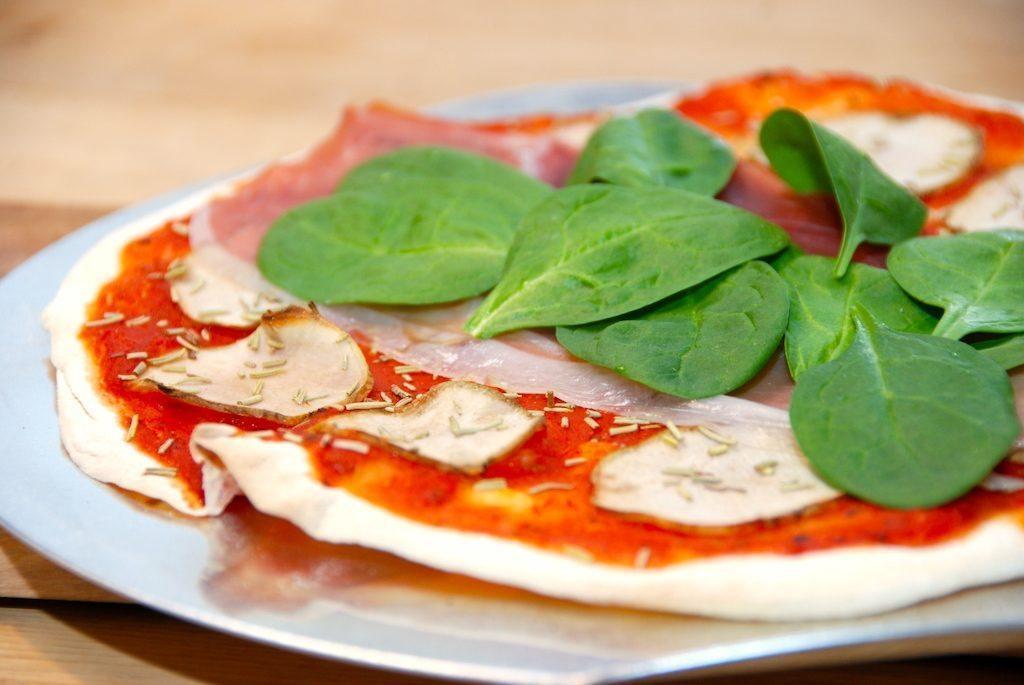 Så let laver du en lækker pizza med jordskokker. Pizzaen skal rulles helt tynd ud, og efter bagning lægges der parmaskinke og spinat på. Foto: Guffeliguf.dk.