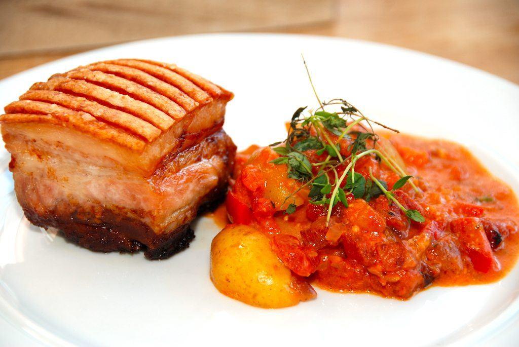 Grillet svinebryst med italienske flødekartofler er mad med masser af smag. Ribbensteg skæres ud i store klumper, og grilles eller steges møre i ovnen, men de italienske flødekartofler laves med kartofler, bacon, løg og tomater. Foto: Guffeliguf.dk.