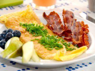 Sådan ser en helt perfekt omelet ud, men det er ikke helt lige meget hvordan du laver den. Her serveret med sprødstegt bacon, purløg, blåbær og pære. Foto: Madensverden.dk.