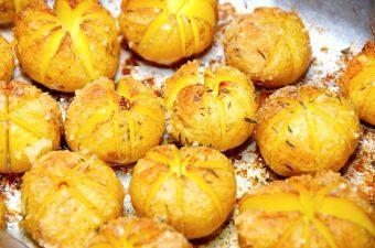 Hasselback kartofler med rasp, der laves af små kartofler, som snittes på skrå. Kartoflerne pensles med smør, og drysses med rasp, salt og timian. Foto: Madensverden.dk.