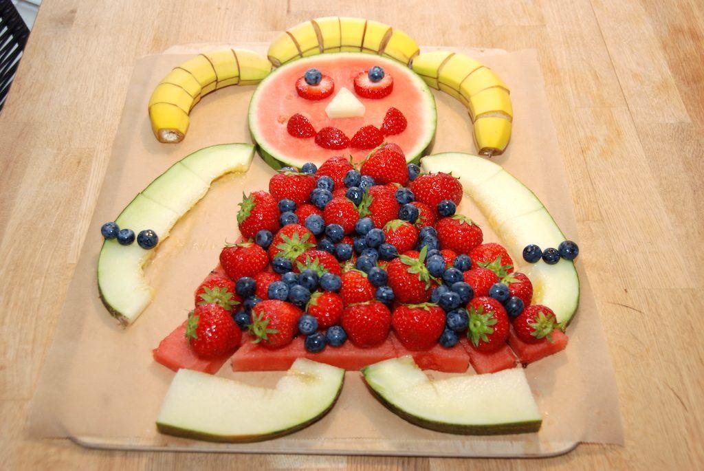 Sådan skal den færdige kagemand af frugt se ud. Med hoved og krop af vandmelon, hår af tre bananer, kjole af jordbær og blåbær, mens arme og ben er lavet af frøskindsmelon. Foto: Madensverden.dk.