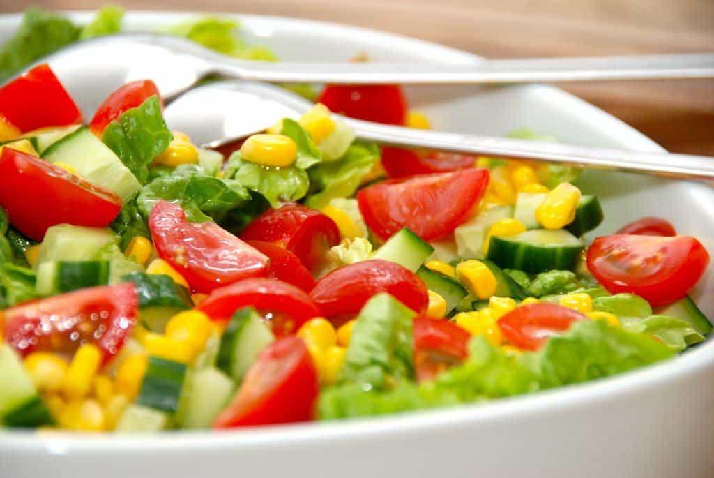 En let og sprød romaine salat med tomater, majs og agurk, der vendes med en hjemmelavet salatdressing. Foto: Madensverden.dk.