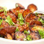Lækre og sprøde hvidløgskartofler i ovn med timian, der er det helt perfekte tilbehør til mange kødretter. Kartoflerne vendes med hvidløg, og bages cirka 40 minutter i ovnen. Foto: Madensverden.dk.