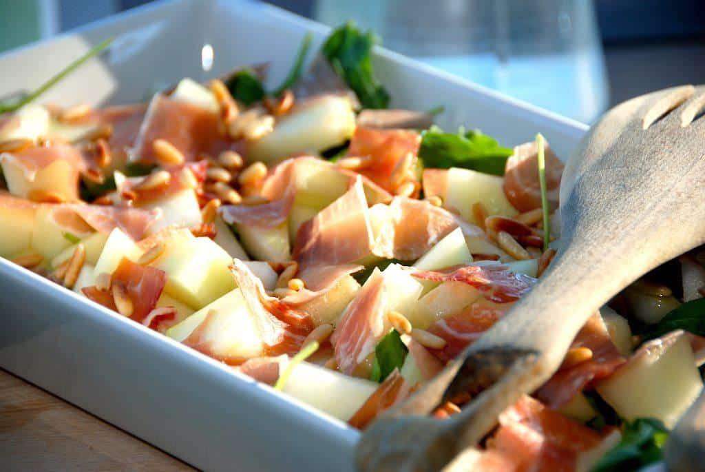 En super dejlig italiensk salat med melon, parmaskinke og pinjekerner, der både kan bruges som en lækker forret, eller som tilbehør til blandt andet kylling. Foto: Madensverden.dk.