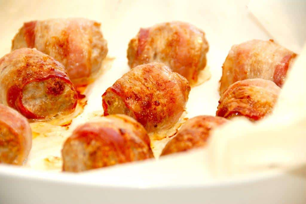 Det er ret nemt at lave disse ovnbagte kødboller med bacon, hvor farskugler omvikles med halve skiver bacon. Derefter bages de 30 minutter i ovnen. Foto: Madensverden.dk.