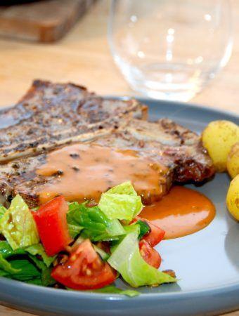 En virkelig lækker og velgrillet T-bone med whiskysauce og romainesalat, som her også er anrettet med nye, danske kartofler. Foto: Madensverden.dk.