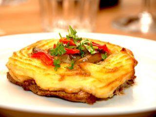 Koteletter med kartoffelmos er en ret i sig selv. Læg en rand af kartoffelmos på koteletterne. og kom en skefuld champignon a la creme i midten, inden du lægger lidt peberfrugt på toppen. Bages 20 minutter i ovnen. Foto: Madensverden.dk.