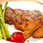 En lækker ret med panerede kartoffelbåde i ovn med ribeye steak og dampede, grønne asparges. De panerede kartofler bliver super sprøde og lækre. Foto: Madensverden.dk.