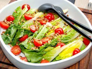 En virkelig lækker og særdeles nem romainesalat med tomater og pinjekerner. Den sprøde salat dryppes med lidt citronsaft og olivenolie. Foto: Madensverden.dk.