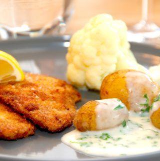 Stegte rødspætter med persillesovs er klassisk dansk mad, og de panerede rødspættefileter er de også fremragende mad. Her serveret med nye kartofler og dampet blomkål. Foto: Madensverden.dk.