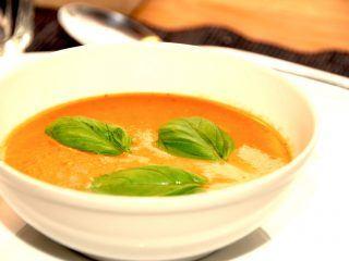 En lækker og og cremet tomatsuppe, der anrettes med friske basilikums blade. Tomatsuppe er god til både forret og hovedret. Foto: Madensverden.dk.