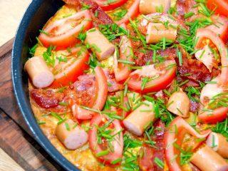 En virkelig lækker kartoffelæggekage med bacon og pølser. Kartoffelæggekagen steges færdig i ovnen, og pyntes desuden med tomater og friskklippet purløg. Madensverden.dk.