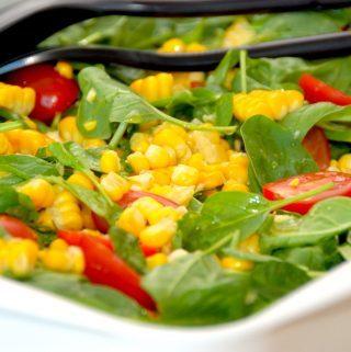 En lækker og sund majssalat med friske majskolber og spinat. Salaten indeholder også tomater, og den vendes med en lækker dressing med honning. Foto: Madensverden.dk.