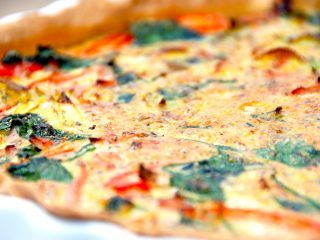 Du skal prøve denne super lækre spinattærte med skinke og porrer. Tærten er nem at lave, og fyldt med spinat, skinke, porrer og rød peberfrugt. Foto: Madensverden.dk.