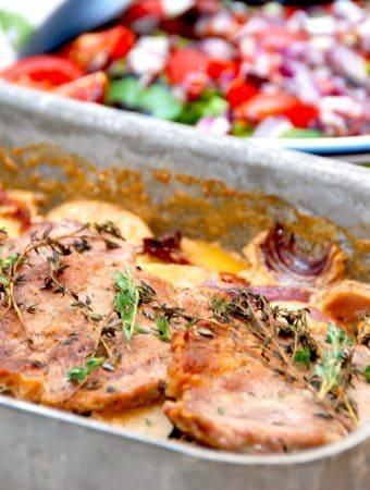 Fadkoteletter med kartofler, løg og flødesovs, der her serveres med en frisk spinatsalat med tomat og rødløg. Foto: Madensverden.dk.