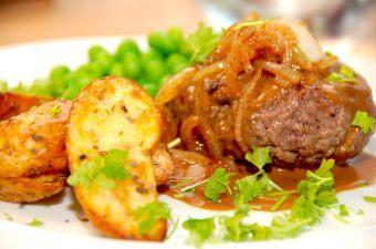 En saftig hakkebøf med brun sovs, de dejlige bløde løg og kogte ærter. Her serveret med ovnstegte aspargeskartofler. Foto: Madensverden.dk.