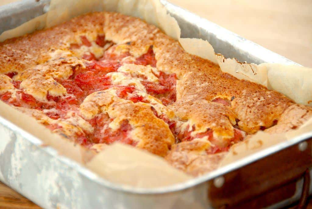 En virkelig læker kage med rabarber, der røres af en luftig dej. Rabarberstykkerne svitses på en pande med lidt sukker og kanel, og derefter bages kagen en time i ovnen. Foto: Madensverden.dk.