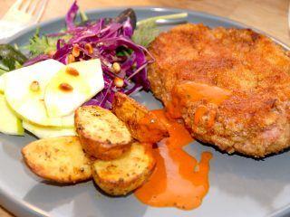 Lækre og panerede nakkekoteletter, der her er serveres med ovnkartofler og en lækker salat. Nakkekoteletterne kan nydes med en hjemmelavet paprikasauce. Foto Madensverden.dk.