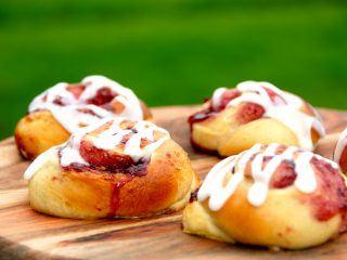 Er der noget bedre end lækre og nybagte hindbærsnegle, der er knap så søde som de almindelige kanelsnegle. Hindbærsenglene pyntes med hvid glasur. Foto: Madensverden.dk.