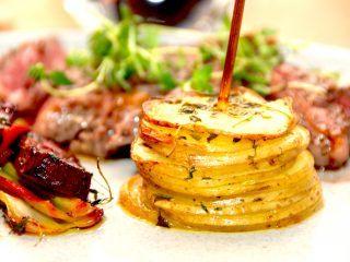 Et flot og lækkert kartoffeltårn, dr laves med skivede bagekartofler, brunet smør og timian. Flot og festligt tilbehør til kødretter. Foto: Madensverden.dk.