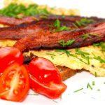 En klassisk omelet opskrift, der laves af æg og lidt paprika, som piskes let sammen med en gaffel. Fyld og tilbehør kan varieres i det uendelige, men her er med tomater, purløg og bacon. Foto: Madensverden.dk.