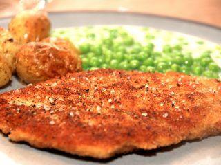 Paneret kylling smager fantastisk godt, og kan sagtens måle sig med en klassisk wienersschnitzel. Her er den serveret me stuvede ærter og ovnbagte kartofler. Foto: Madensverden.dk.