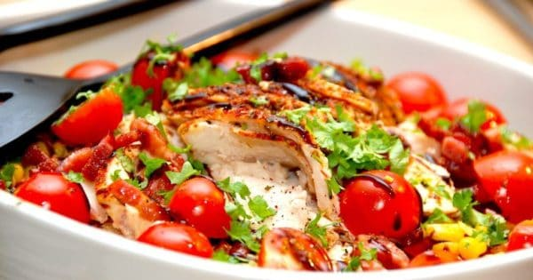 En sund og nem kyllingesalat med bacon og lækre grøntsager. Kyllingesalaten laves blandt andet med tomater og forårsløg, og dryppes med olivenolie og balsamico. Foto: Madensverden.dk.