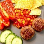 En dejlig og lækker tallerken med mexicanske frikadeller, hjemmelavet majssalsa og tortilla chips. Dertil serveres friske skiver af agurk og en bagt peberfrugt. Foto: Madensverden.dk.