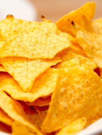 Nachos med cheddarost laves af de sprøde tortilla chips, der jo er lavet af majs. Ved at lave dem i oven er du sikker på sprøde nachos med den helt rigtige og klæbrige ost. Foto: Madensverden.dk.