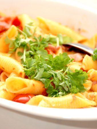 En super lækker og nem pasta opskrift med bacon og cherrytomater på dåse, der koges med lidt fløde. Pasta vendes i og der pyntes med lidt persille. Foto: Madensverden.dk.