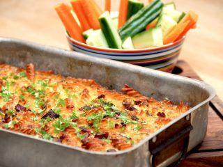 Et lækkert pastafad med bacon, der er serveret med gnavegrønt i form af gulerødder og agurk og stave. Pastafadet bages cirka 50 minutter i ovnen. Foto: Madensverden.dk.