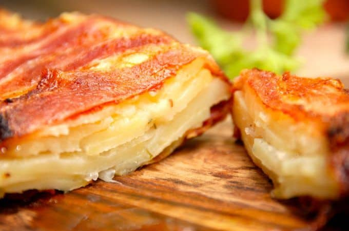 En lækker kartoffelkage med bacon, der er super lækker tilbehør til både en bøf eller oksesteg. Kartoffelkagen pakkes ind i skiver af bacon, hvorefter den bages en times tid i ovnen. Foto: Madensverden.dk.