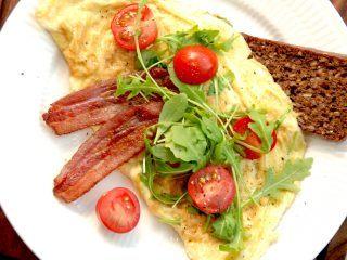 Sådan en omelet med rucola er en nem omelet til morgenbordet eller en brunch, og du skal beregne to æg pr. omelet. Her er omeletten serveret med sprødstegt bacon og små tomater. Foto: Madensverden.dk.