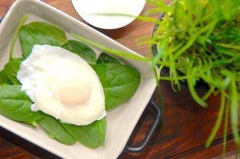 Pocheret æg lyder måske lidt bøvlet at lave, men det er faktisk ganske nemt. Ægget koges i vand i tre minutter, og så skal du sådan set ikke gøre så meget mere. Det er ikke nødvendigt at røre i vandet, eller at tilsætte eddike. Her er det pocherede æg anrettet på lidt frisk spinat. Foto: Madensverden.dk.