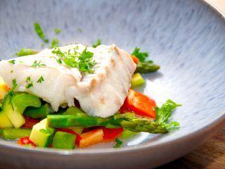 dampet torsk er nem at lave i ovnen, og her er torsken anrettet på en bund af sauterede grøntsager. En meget nem ret med fisk som de fleste ville kunnet lide. Foto: Madenservden.dk.