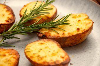 Halve bagte kartofler er nemt tilbehør, og de er lidt hurtigere at lave end de normale bagekartofler. Kartoflerne pensles med en hvidløgsolie, hvorefter de bages cirka 35 minutter i ovnen. Foto: Madensverden.dk.