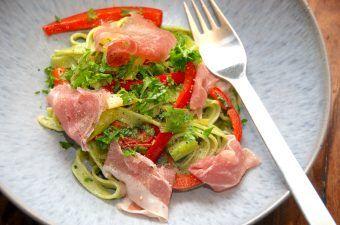 Spinatpasta er en lækker pasta, der jo som navnet antyder, indeholder en del spinat, og deraf den grønne farve. Her er den vendt med stegte peberfrugter og andre lækre sager, og det er en dejlig aftensmad. Foto: Madensverden.dk.