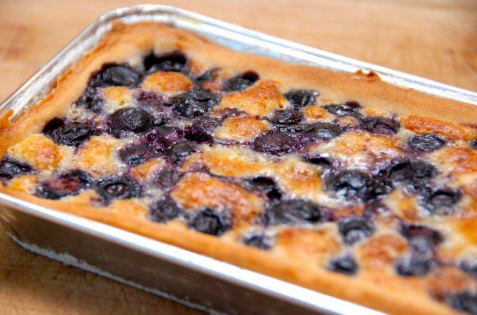 En lækker og hjemmebagt blåbærtærte, der både kan bages med friske og frosne blåbær. Tærten laves af en nem mørdej og mazarinmasse, inden du øverst lægger et lag blåbær. Her har jeg bagt den i en aflang form, men blåbærtærten kan også laves i en almindelig tærteform. Foto: Madensverden.dk.