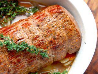 En langtidsstegt roastbeef skal steges i cirka seks timer i ovnen ved lav temperatur, men så får du også et virkelig godt stykke kød. Kødet brunes og kommes i fad sammen med blandt andet frisk timian. Foto: Madensverden.dk.