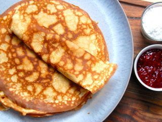 Mormors pandekage opskrift giver nogle skønne, sprøde og tynde pandekager, præcist som pandekager skal være. Her er de serveret med hindbærsyltetøj og flormelis. Foto: Madensverden.dk.