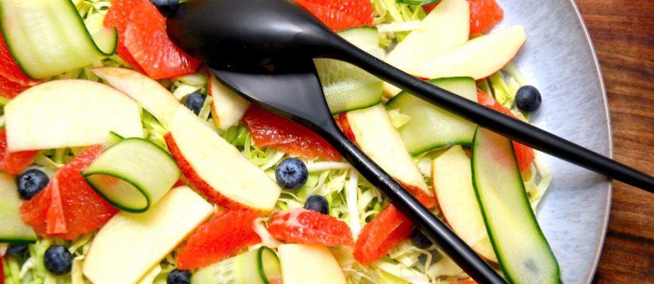 En skøn spidskålssalat med grape, der både er smuk og sund. Salaten laves med fintsnittet spidskål, der arrangeres med stykker af rød grapefrugt, blåbær, æble og tynder skiver agurk. Du kan dryppe salaten med lidt olivenolie - eller lade være. Den er fin som den er. Foto: Madensverden.dk.