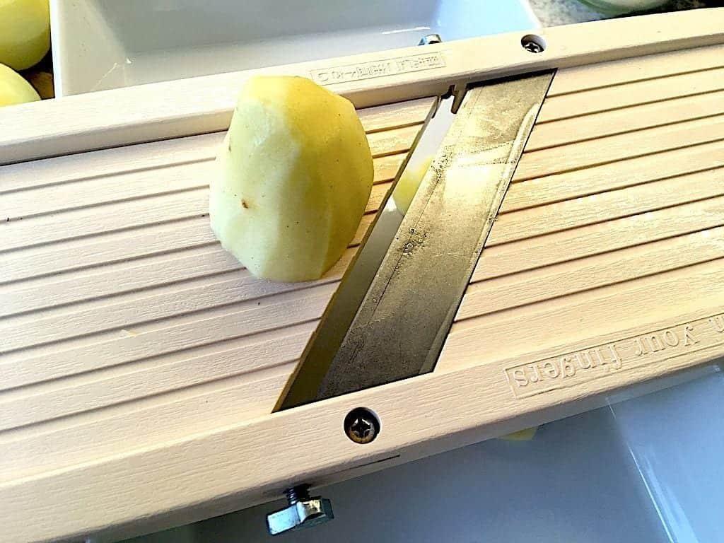 billede med kartoffel på mandolinjern til flødekartofler