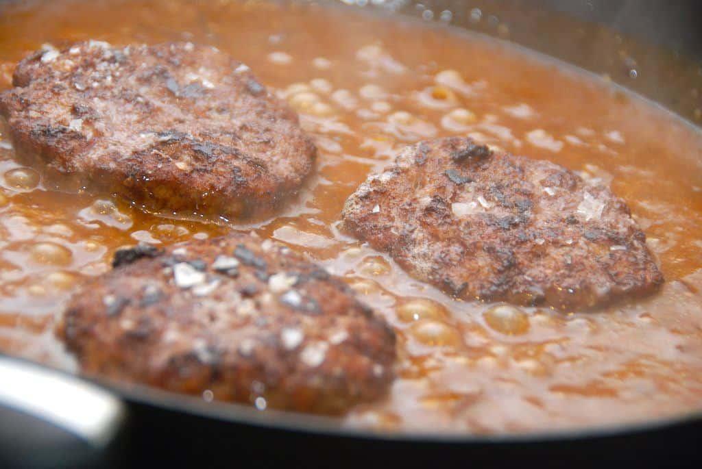 Burgerbøfferne varmes med i den færdige sovs i fem minutter inden de skal i en lækker bøfsandwich. Foto: Madensverden.dk.