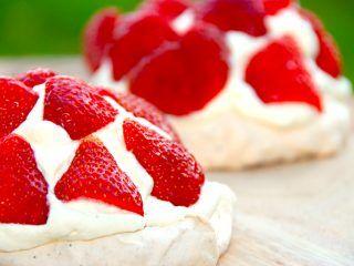 Lækre og indbydende mini pavlova med jordbær og cremet flødeskum, der er tilsat vanilje. Kagerne er nemme at bage, og de smager fantastisk godt. Foto: Madensverden.dk.